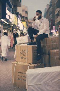 Homme assis sur des cartons de déménagement
