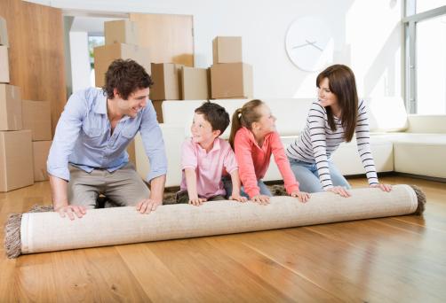 famille en train de dérouler un tapis pendant un déménagement
