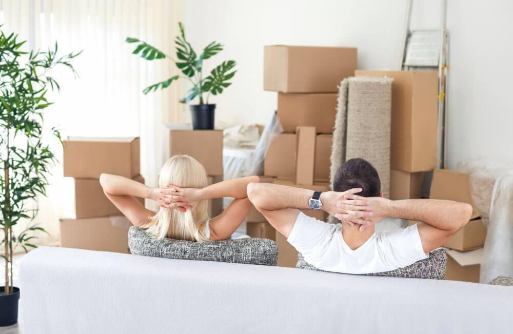 Un homme et une femme vus de dos assis dans un canapé et regardant des cartons de déménagement